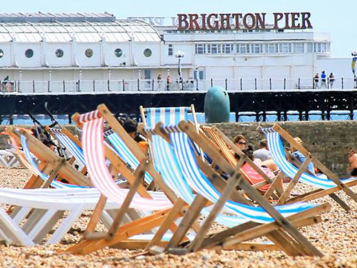Deck chairs on the shore of Brighton Beach with Brighton Pier in the background