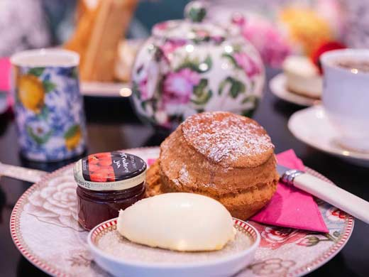 scone on a plate with jam and clotted cream at B Bakery