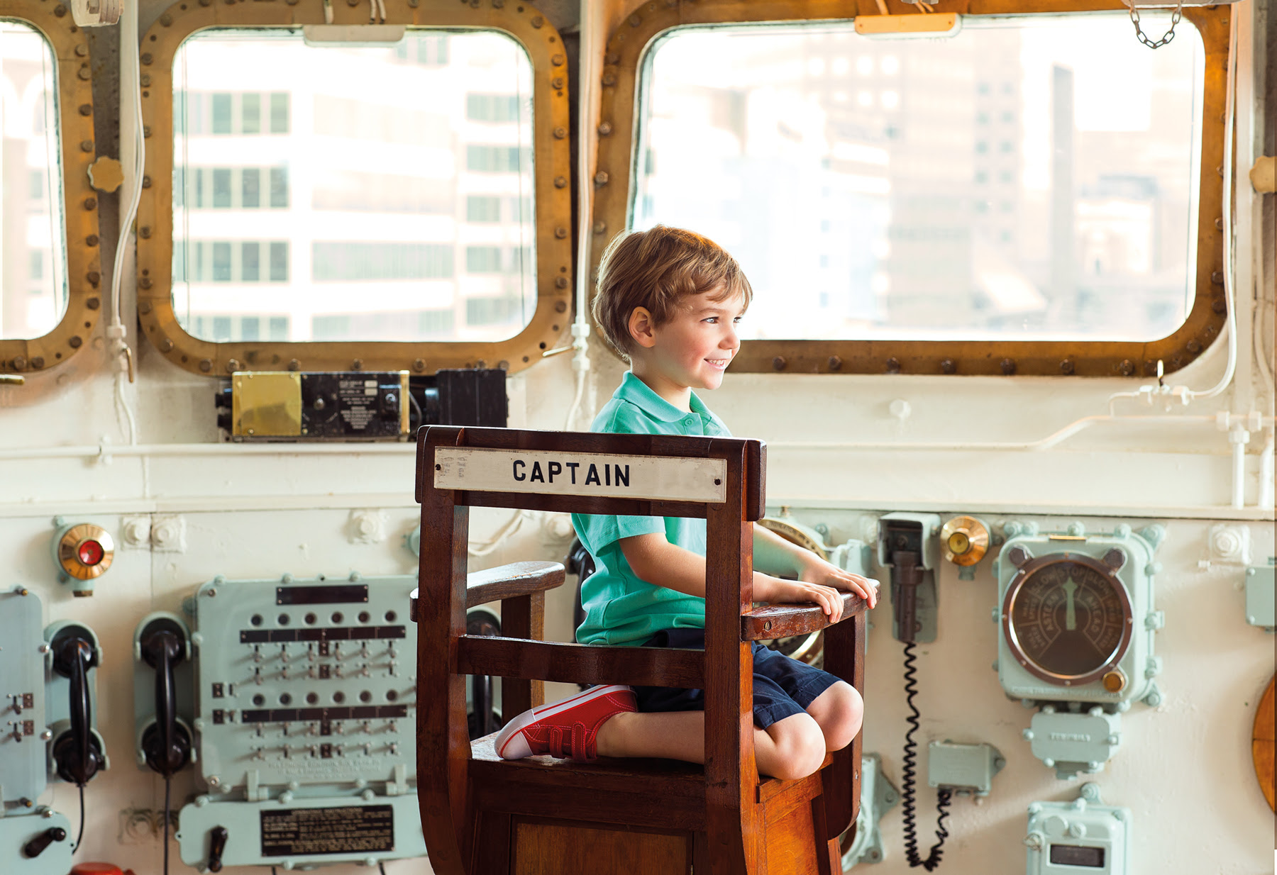 little boy in captain's seat on ship