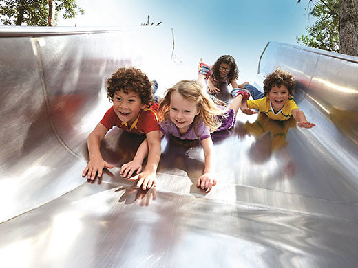 kids sliding down a slide at Queen Elizabeth Olympic Park