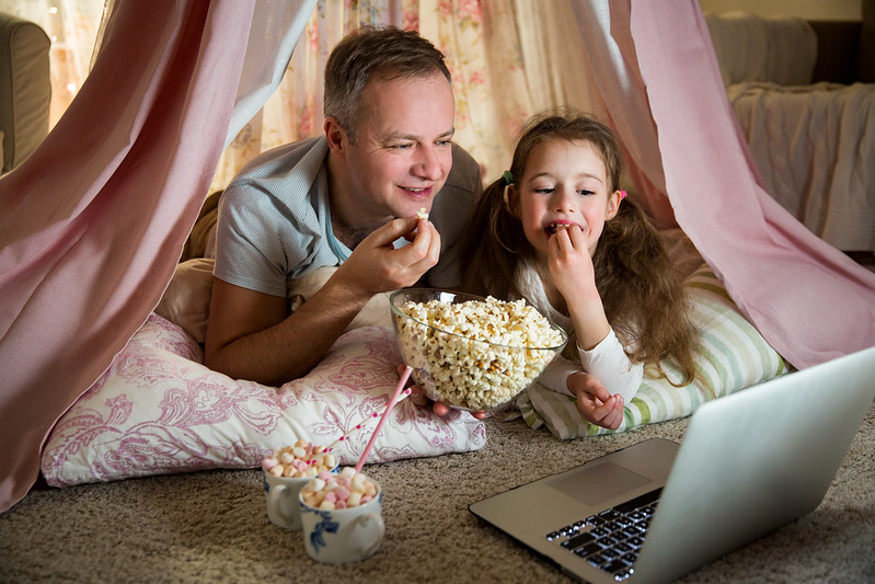Father and daughter watching a musical in their indoor fort.