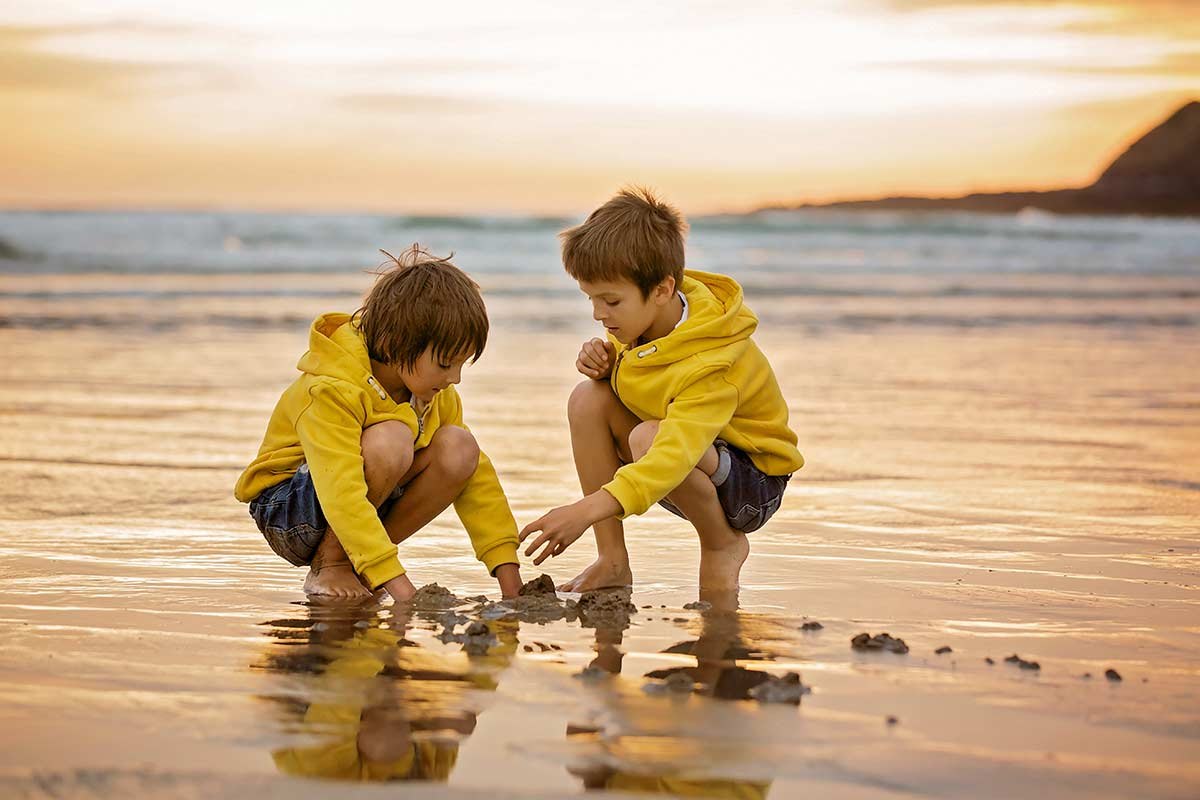 Two boys playing at the seaside on a cooler day.