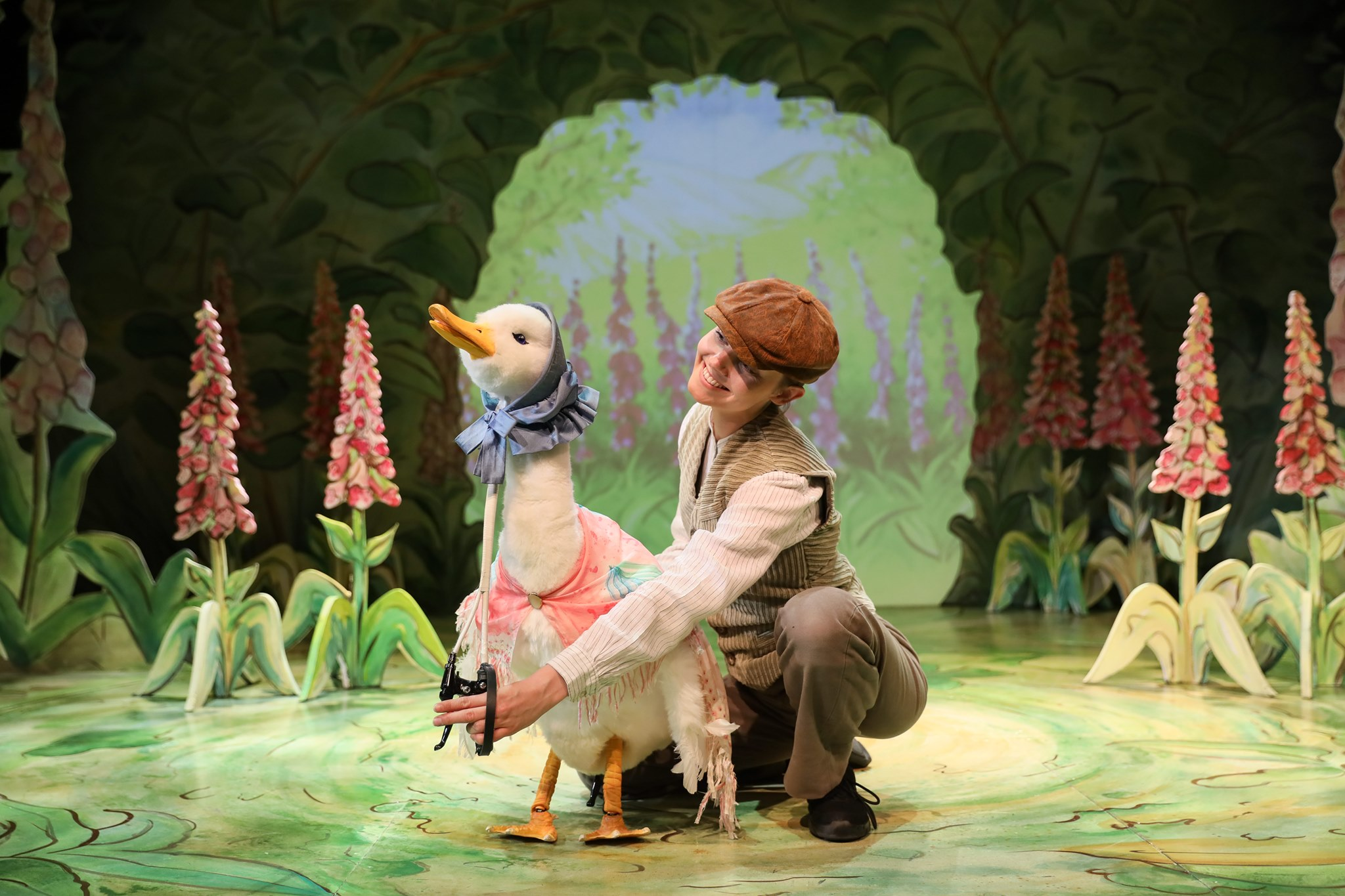 a swan puppet on stage amongst trees