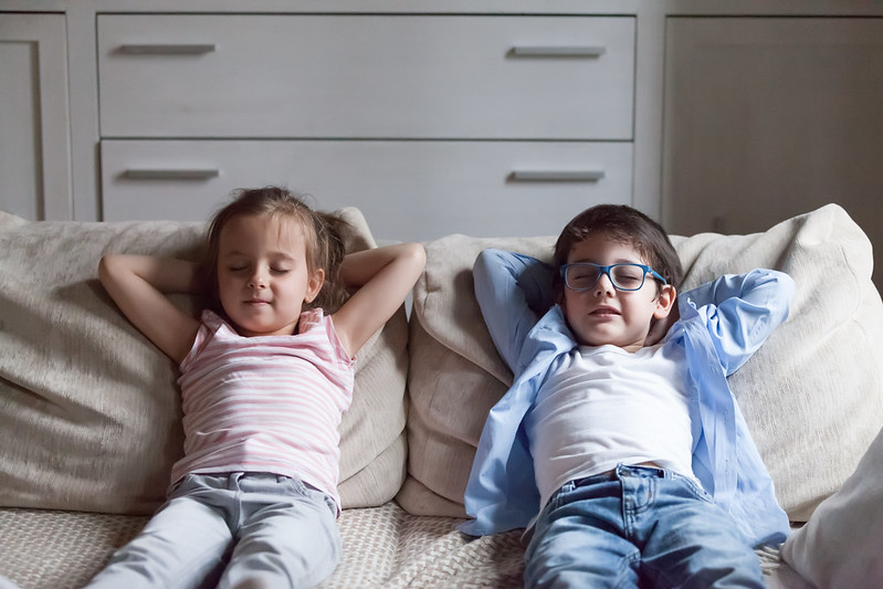 Two kids relaxing on the sofa in the living room.
