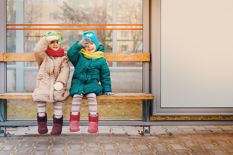 Two girls waiting for the bus in winter