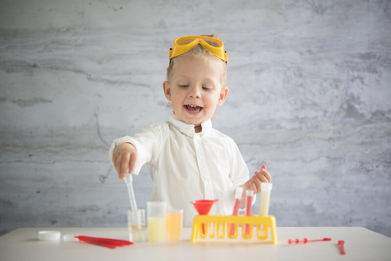 Young child who loves STEM does a science experiment at home.