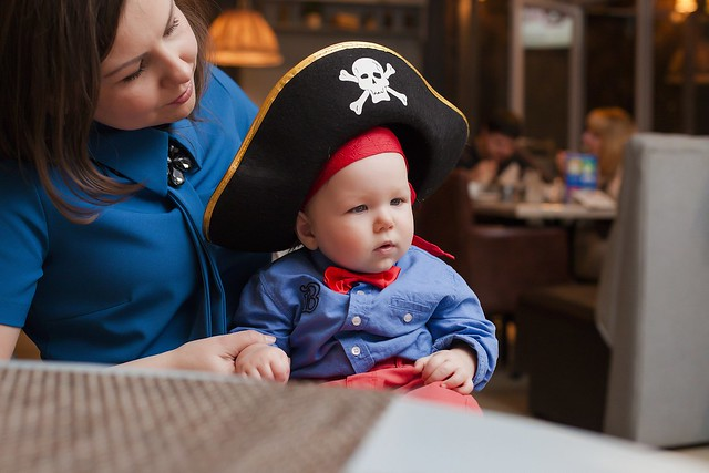 A baby tries on a pirate hat on the golden hinde
