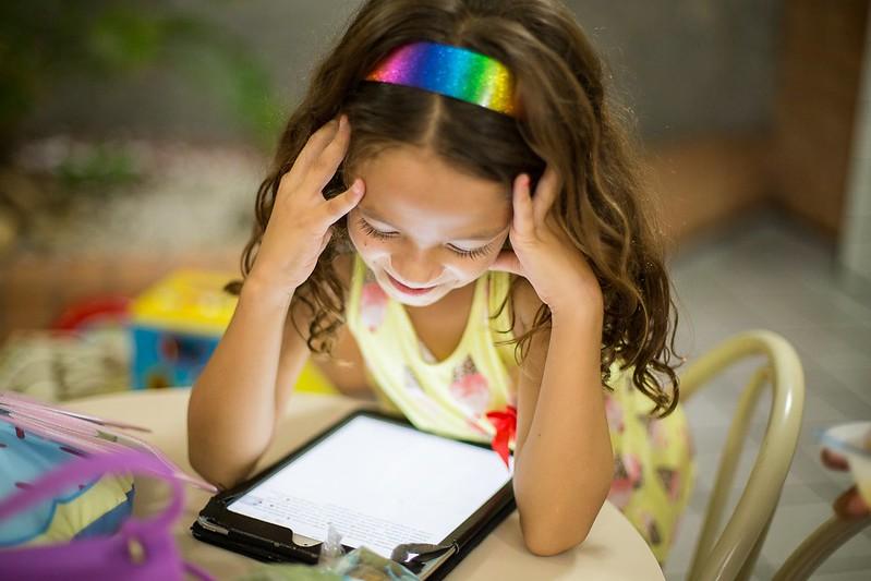 Girl with rainbow headband looking at unicorn jokes