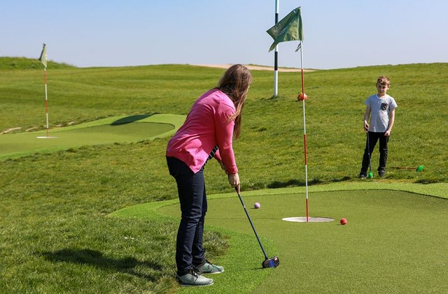 Woman playing golf on a golf course like the one at Golf Kingdom.