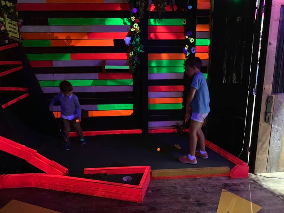 two boys playing mini golf on a colourful neon golf course