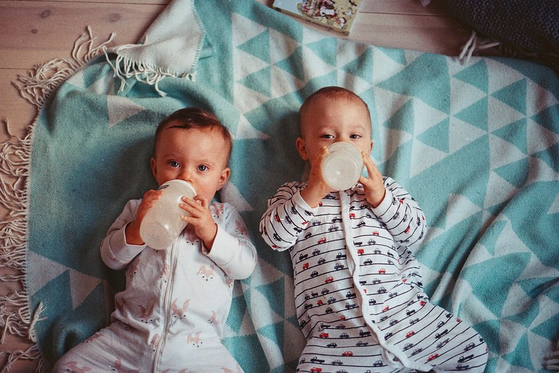 Two babies learning how to feed themselves from a bottle.