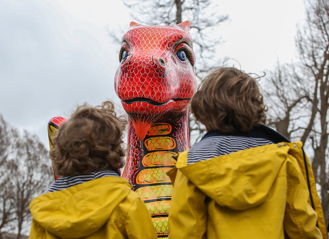 Two children looking at a sculpture of a dinosaur