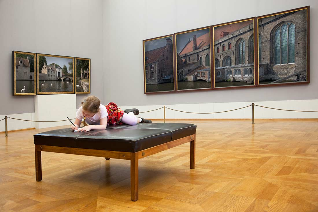 Child doing activity on a bench at an art gallery.