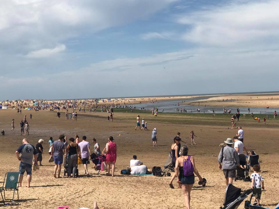 a busy norfolk beach on a hot summers day