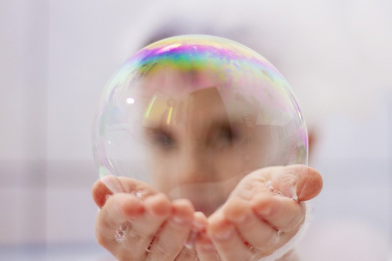 Boy looking through a bubble