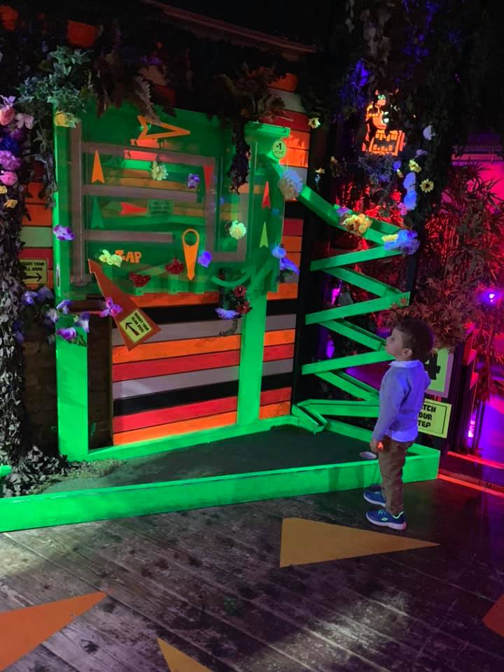 boy on a neon golf course at plonk crazy golf in camden