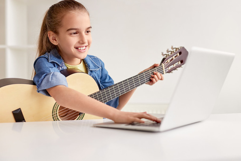 Child learning the guitar.