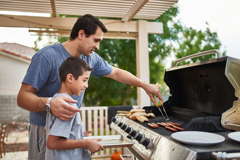 Father showing his son how to cook using the BBQ.