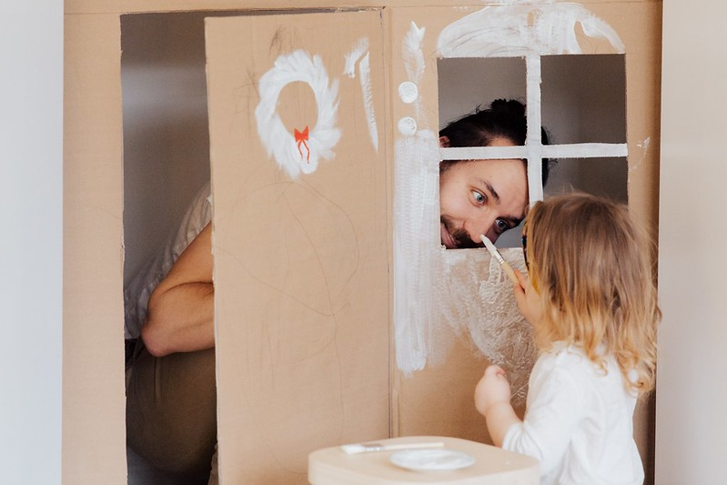 Playing in a DIY cardboard house at home.