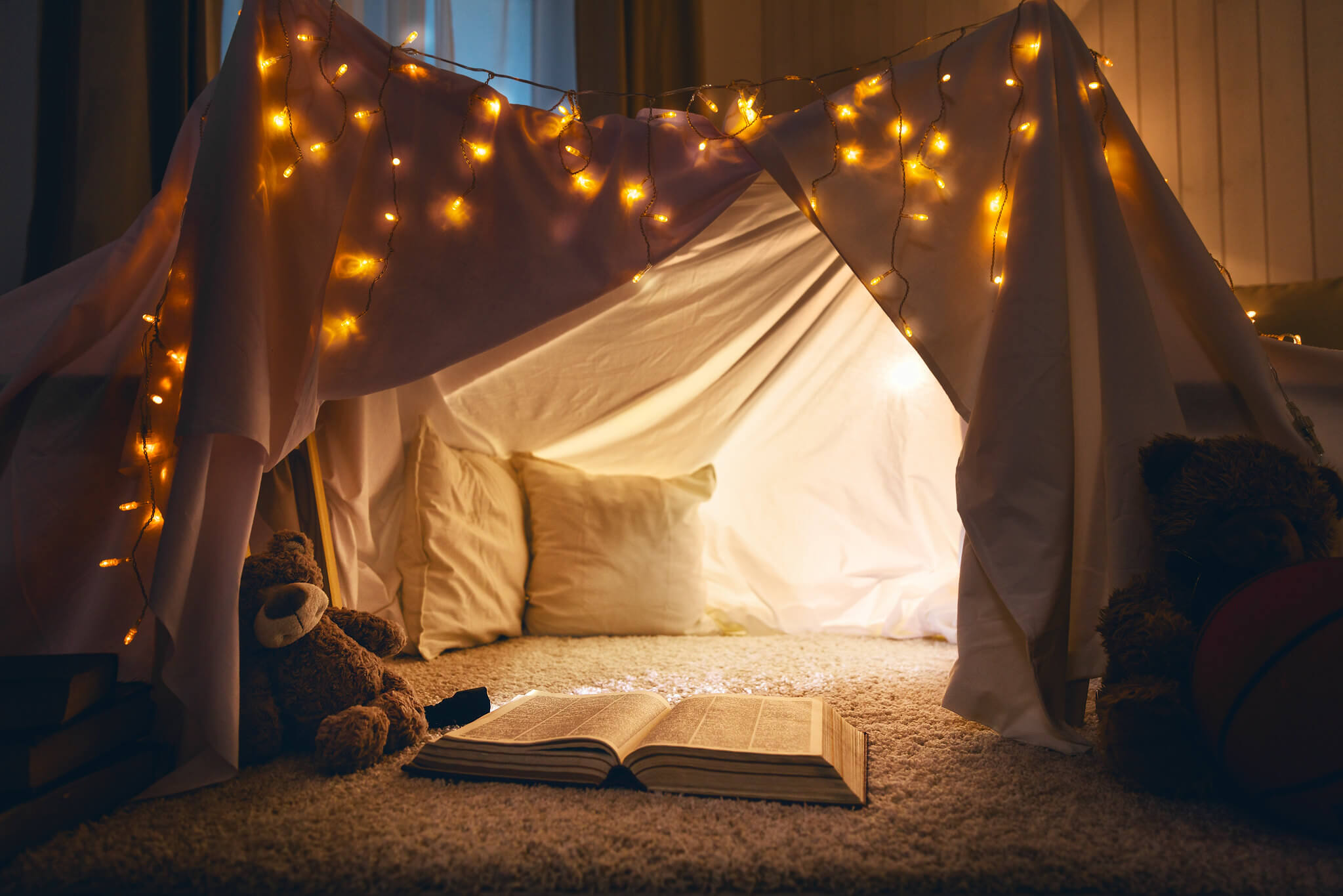 Set up a reading den in your living room, complete with fairy lights and cosy blankets.