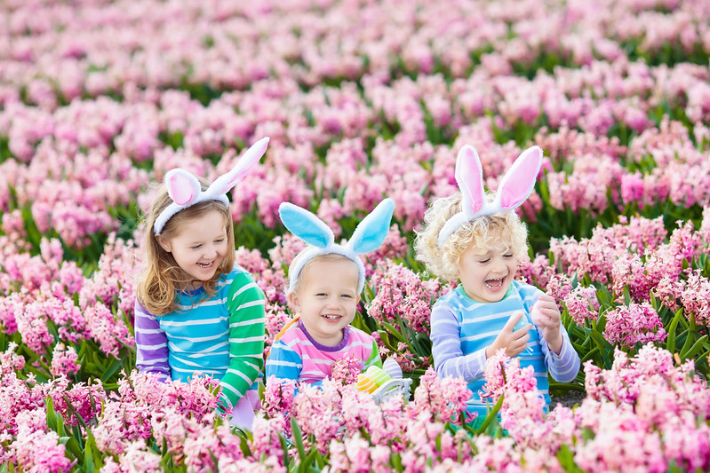 Kids dressed as the Easter bunny in a field of flowers.