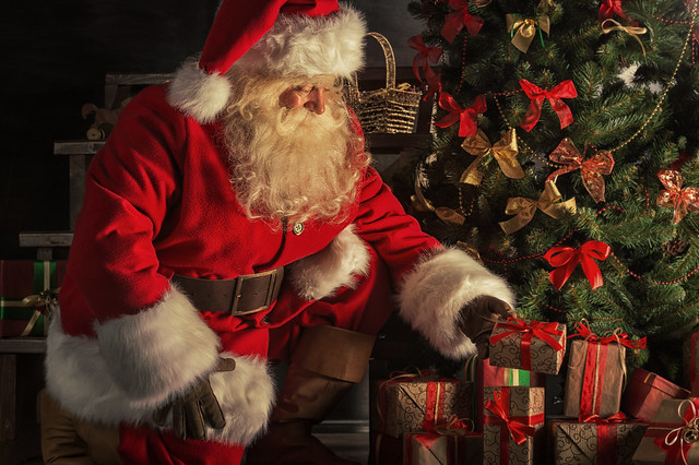 Santa Claus placing gifts under the Christmas tree