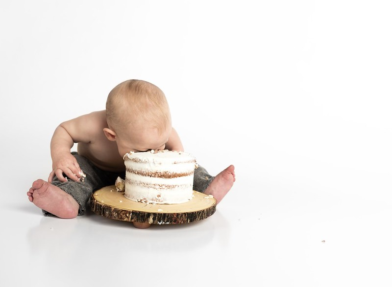 Toddler with their face in a large cake, taking a bite.