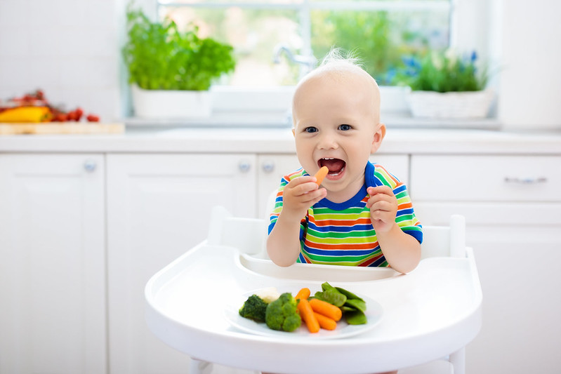 Cute baby boy eating vegetables.