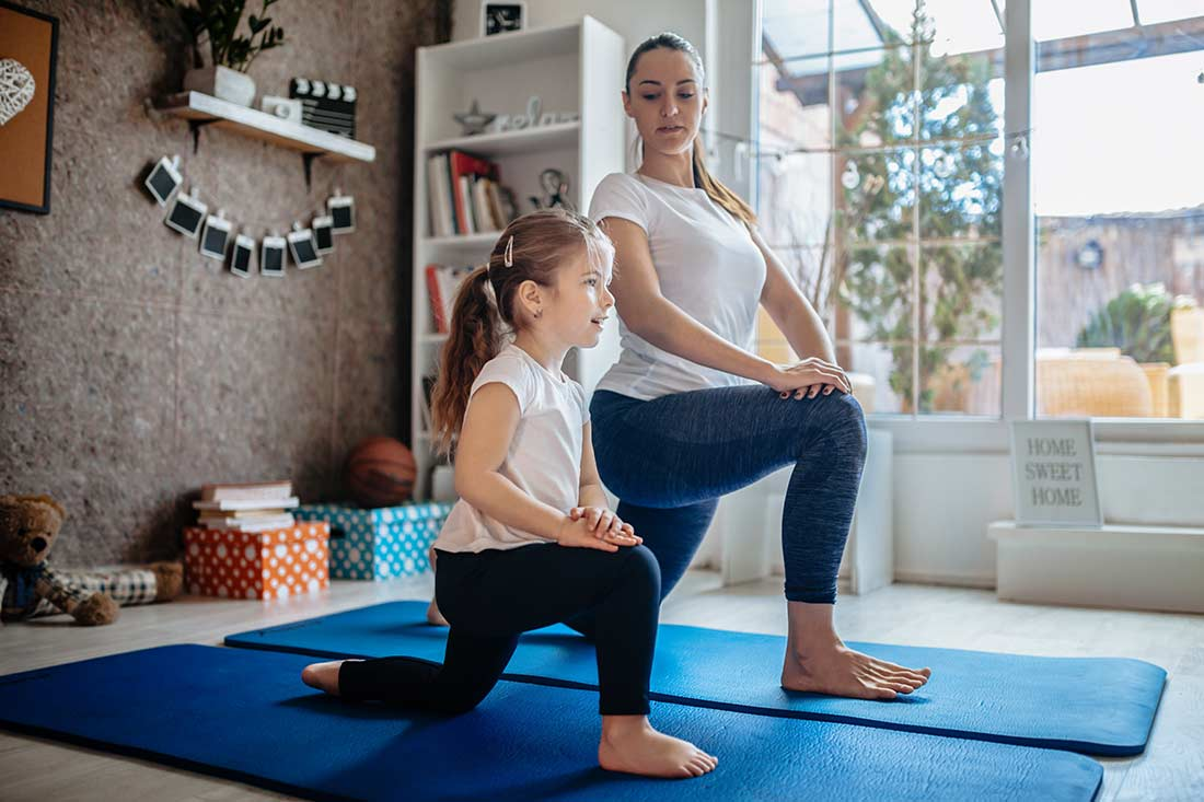 Mother and daughter practising yoga at home.