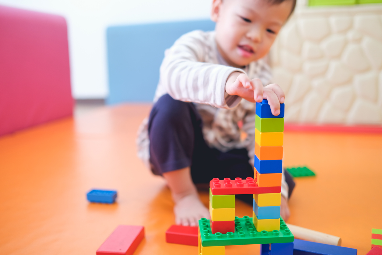 Toddler playing with building blocks.