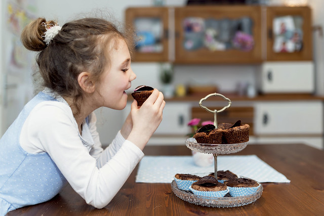 girl eating a cupcake off a stand