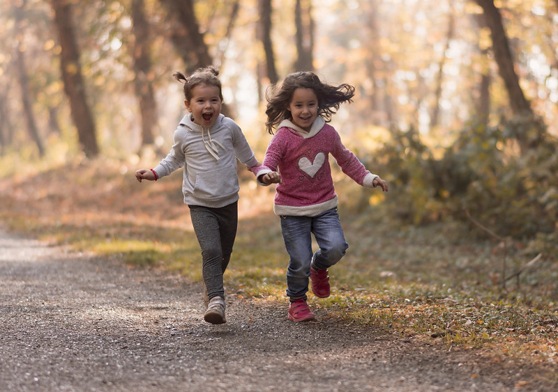 Two young girls running through a forest.