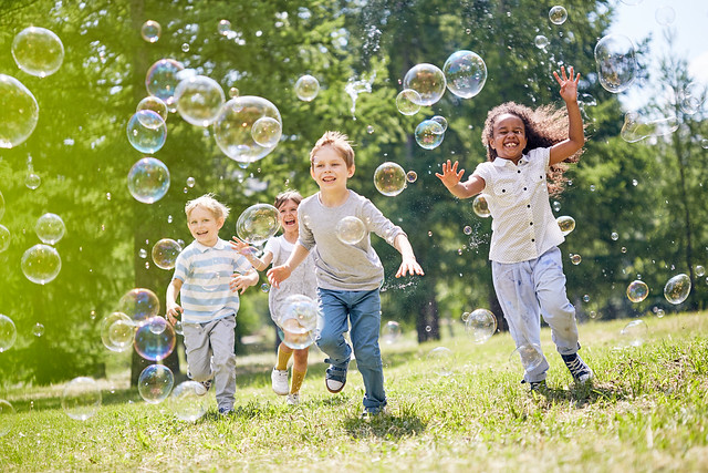 Group of children running through a park chasing bubbles.