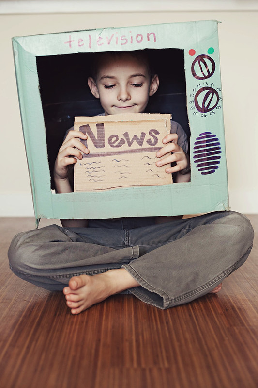 Boy pretending to be on the news in a cardboard telly.