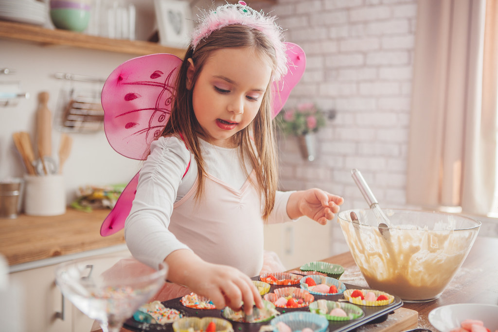 Young girl dressed as a fairy baking rainbow-inspired food.
