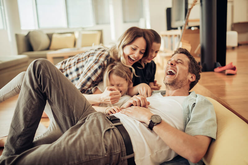 A family laughing together in their living room.