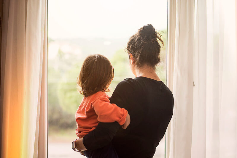 A mother carrying her daughter as they look out the window during lockdown.