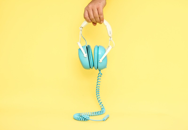 A pair of blue headphones against a yellow background.