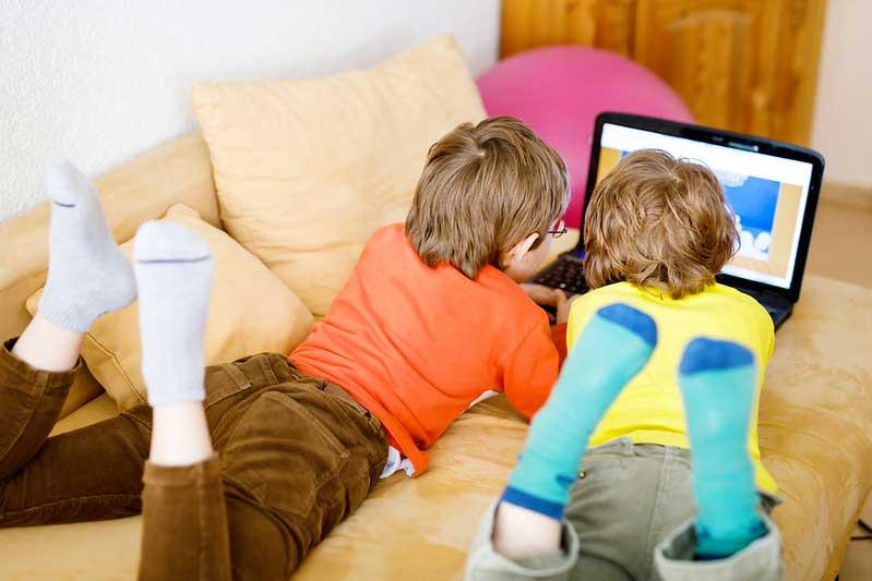 Two kids in KS2 watching an educational TV programme.