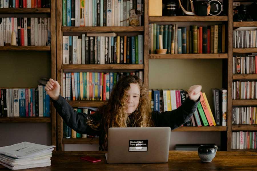 teenage girl celebrating at her laptop