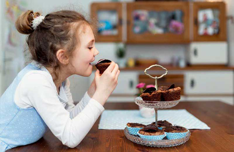 Young girl enjoying a homemade chocolate cupcake.