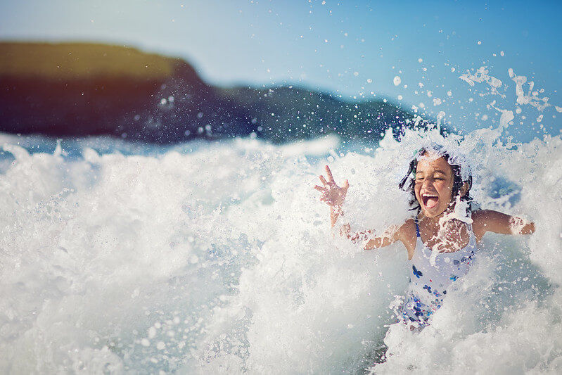 Girl enjoying being splashed in the ocean