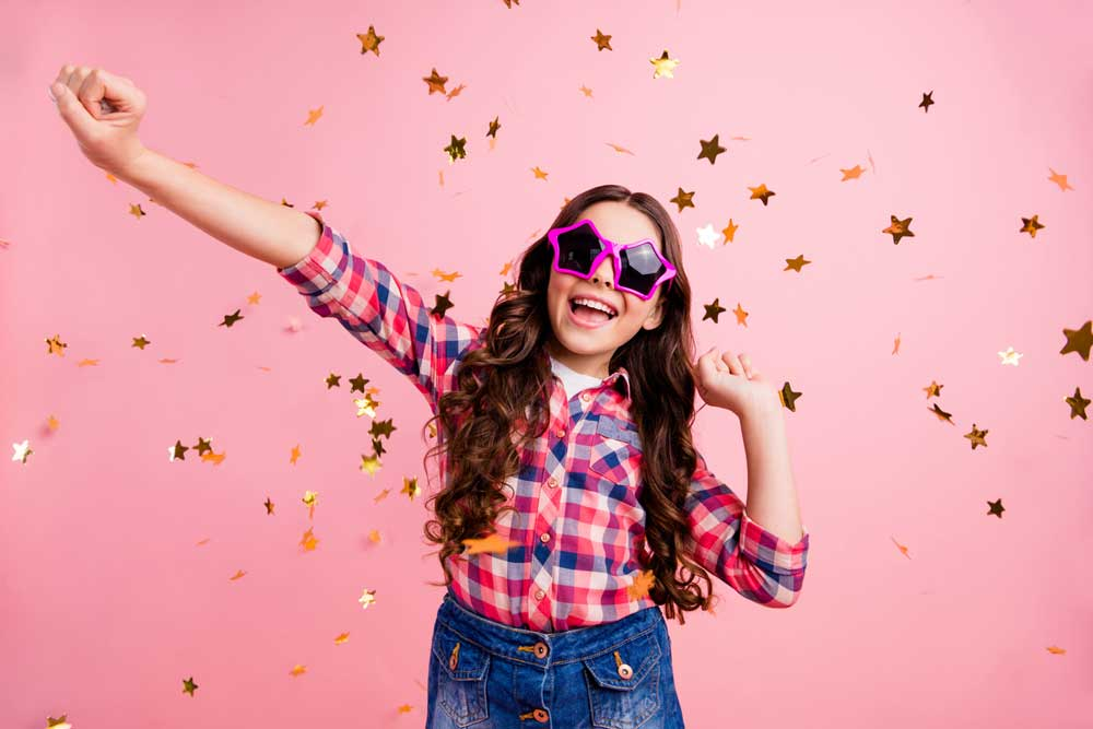 girl wearing star-shaped sunglasses showered with gold star confetti