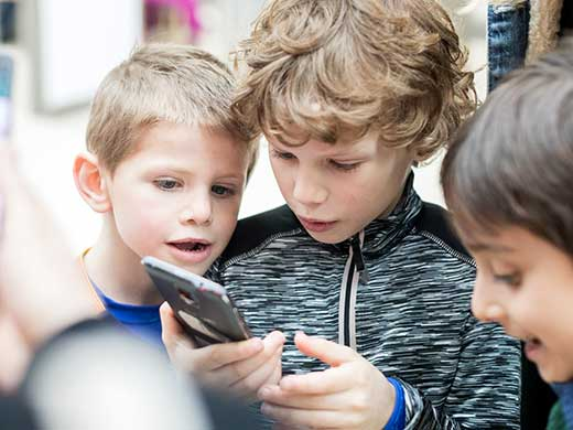 Kids looking at a phone for the text quest.