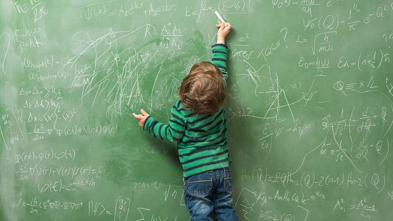 A young boy practises maths equations on a blackboard.