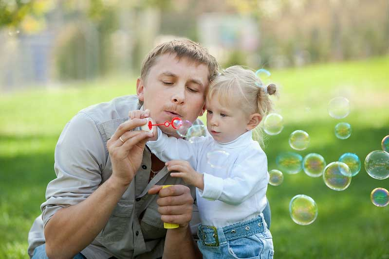 Playing with bubbles is a great calming activity for your toddler.
