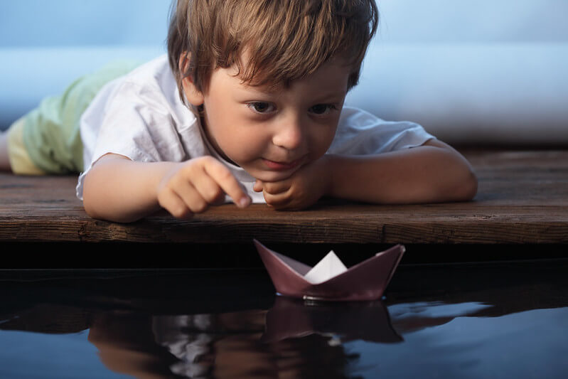 Child testing out their boat made from aluminium foil