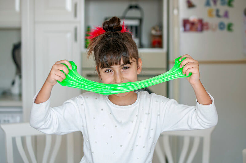 Girl playing with neon green slime.