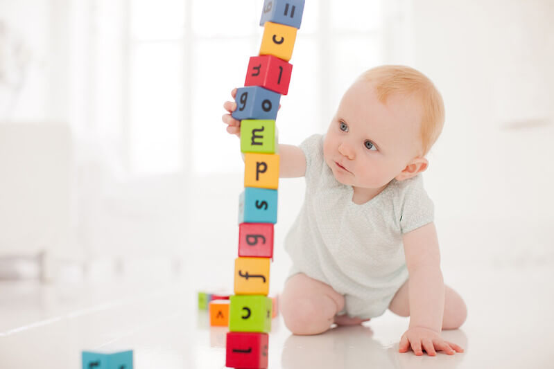 Toddler looking at building blocks.