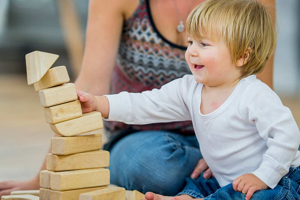 young boy playing with building blocks
